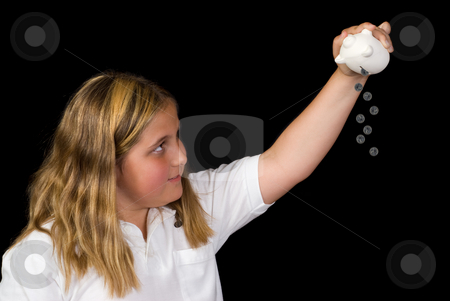 Child Emptying Piggy Bank stock photo, A young girl is pouring money out of her piggy bank, isolated against a black background by Richard Nelson