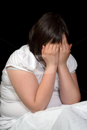 Crying Girl stock photo, A young preteen girl sitting in the dark and crying with her hands covering her face by Richard Nelson