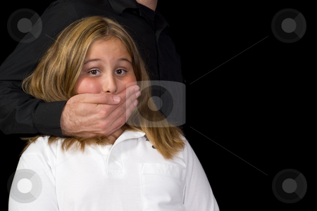 Kidnapping stock photo, A young girl standing scared with a hand covering her mouth so she can't scream, isolated against a black background with copyspace by Richard Nelson