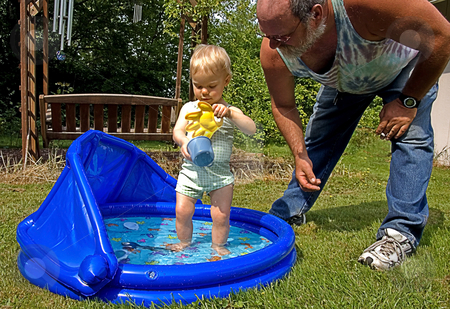 Grandpa and Granddaughter Summertime Fun stock photo, This grandpa is helping toddler granddaughter in a kiddie pool for summer time fun. by Valerie Garner
