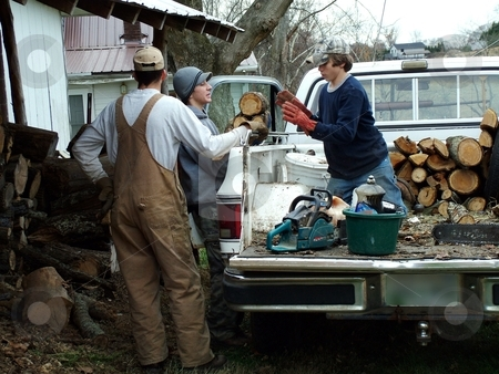 Father and Sons stock photo, This father works with his two sons stacking wood for the cold winter months. by Krystal McCammon