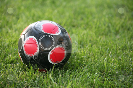 Soccer ball stock photo, Black white and red soccer ball on a natural grass background by Stacy Barnett