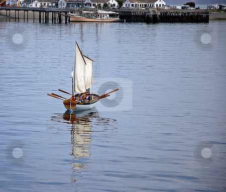 Sailboat With Oars on Ocean stock photo, This sailboat has a unique look with many oars out and people aboard, floating on the ocean with the shore in the background. by Valerie Garner