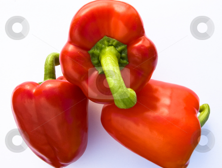 3 red bell peppers stock photo, Overhead shot of 3 red bell peppers on white background by Christian Rhein