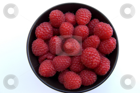 Raspberries in bowl  stock photo, Overhead shot of fresh red raspberries in black bowl on white background by Christian Rhein