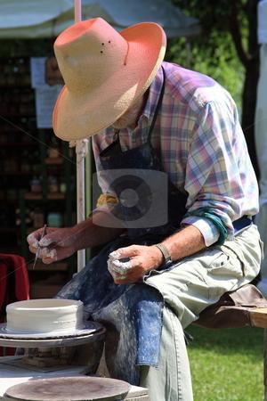 Pottery Maker stock photo, Potterer sculpting  clay pot for sale at a flea market by Jack Schiffer