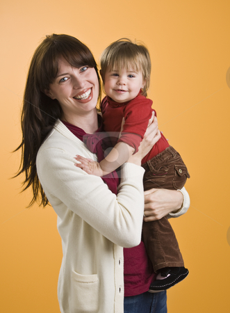 Woman Holding Toddler stock photo, A young woman is holding a toddler and smiling at the camera.  Vertically framed shot. by Jonathan Ross