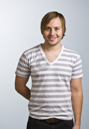 Man Smiling at Camera stock photo, A young man wearing a striped shirt is smiling at the camera.  Vertically framed shot. by Jonathan Ross