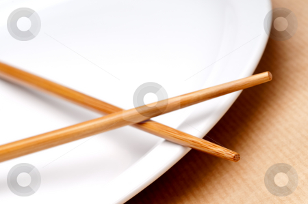 A tilted horizontal macro of a pair of chopsticks on a white pla stock photo, A tilted horizontal macro of a pair of chopsticks on a white plate by Vince Clements