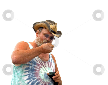 Middle Aged Man With Chewing Tobacco stock photo, This middle aged man wearing a cowboy hat and tie dyed shirt is taking a dip of chewing tobacco. by Valerie Garner