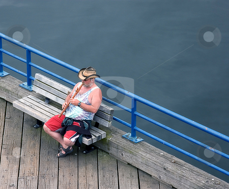Man Playing Wooden Flute on Dock stock photo, This middle aged Caucasian man is playing a wooden Native American flute on a dock. by Valerie Garner