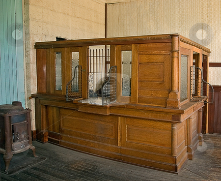 Antique Bank Teller Station stock photo, This antique bank teller station is an authentic replication with old wooden floors and wood stove to the old black typewriter in the background. by Valerie Garner