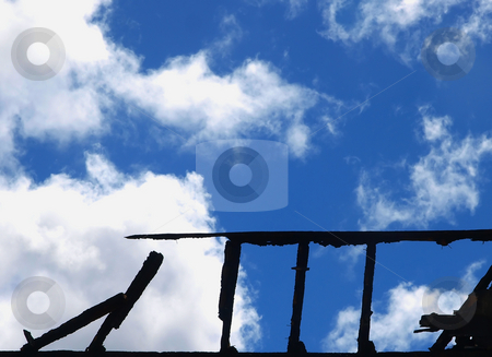 Fire Damaged stock photo, Silhouette of Charred Wall against a cloudy sky by Margo Harrison