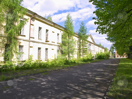 Building and road stock photo, Long low-rise building with the road and trees at the sunny day by Sergej Razvodovskij