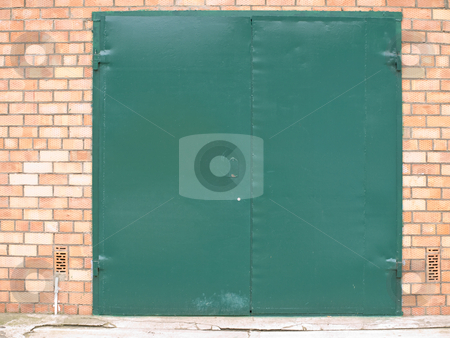 Metallic door stock photo, Green metalic door in the bicks wall by Sergej Razvodovskij