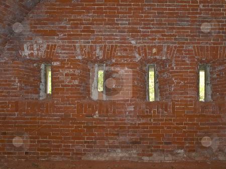 Loopholes stock photo, Row of narrow loopholes in the red brick wall by Sergej Razvodovskij