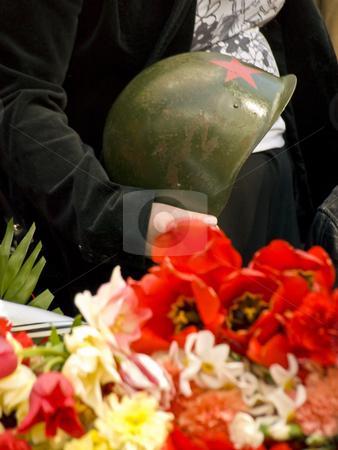 Soldier hat stock photo, Old metal russian oldier hat in hands near the flowers by Sergej Razvodovskij