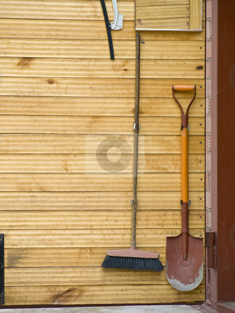 Shovel and broom stock photo, Domestic tools shovel and broom at the wooden door by Sergej Razvodovskij