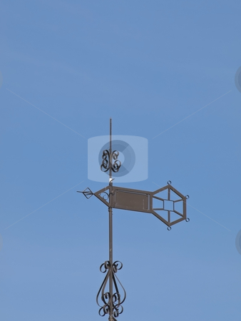 Weather vane stock photo, Metallic weather vane against the blue sky by Sergej Razvodovskij