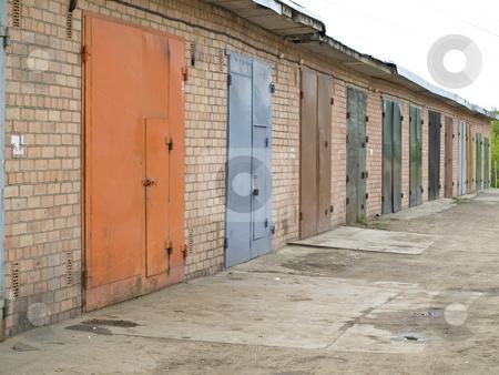 Garage row stock photo, Row of garage with multicolored metalic doors by Sergej Razvodovskij