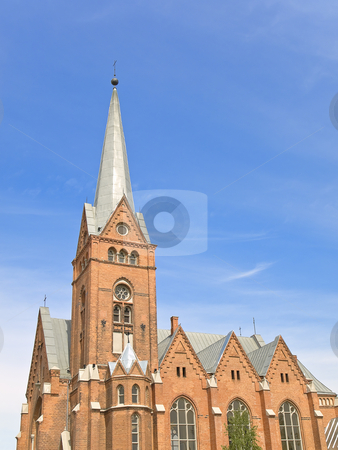 Red Church  stock photo, Red brick Church against the blue cloudy sky by Sergej Razvodovskij