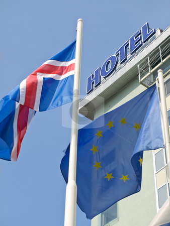 Flags near hotel stock photo, Blue yellow European flag with other fluttering in front of the hotel by Sergej Razvodovskij
