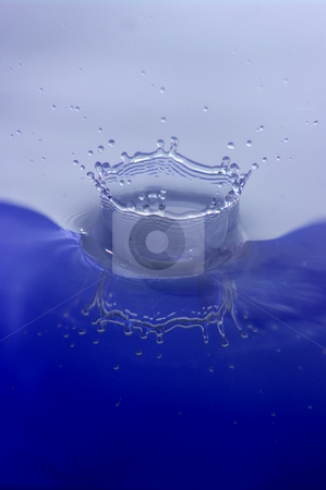 Splash stock photo, A high speed shot of a droplet of water, frozen as it hits the liquid surface. by Martin Darley