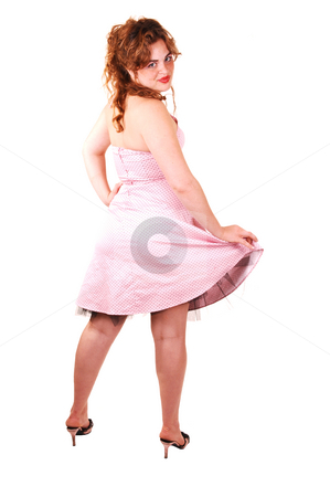 Pretty girl in pink dress. stock photo, Young lovely girl in a pink dress and red long hair standing with her back to the camera, looking over her shoulder, on white background. by Horst Petzold