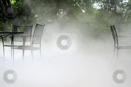 Chairs In The Fog stock photo, Wrought Iron table and chairs on a patio covered with ground fog by Lynn Bendickson