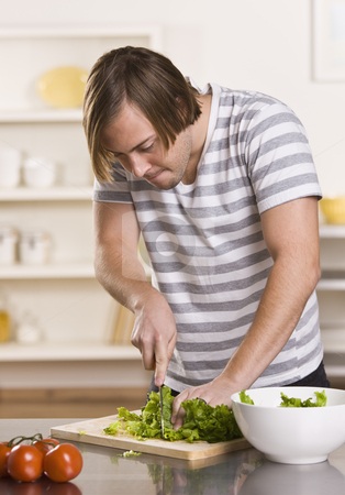 Attractive male cutting lettuce stock photo, Attractive male cutting lettuce, making a salad on the kitchen counter. White bowl to his side and he is wearing a striped shirt. vertical by Jonathan Ross