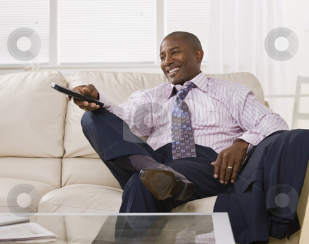 Attractive African American Man watching TV stock photo, Attractive African America watching TV and laughing, while sitting on a coach dressed in a shirt and tie. square by Jonathan Ross