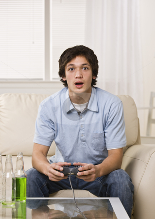 Cute guy playing video game stock photo, Cute guy playing video game while sitting on the coach drinking a lot of green soda. Vertical by Jonathan Ross