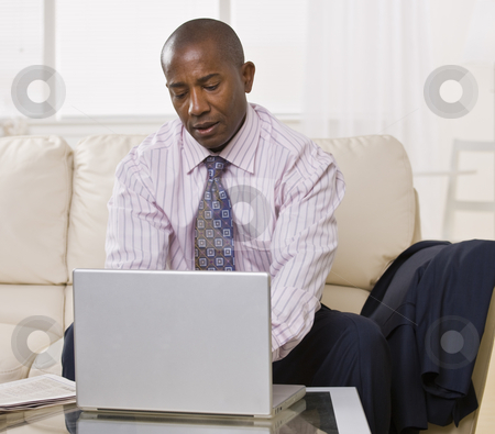 African American male with laptop stock photo, African American male using a laptop on a coffee table. He is looking at the laptop. Square. by Jonathan Ross