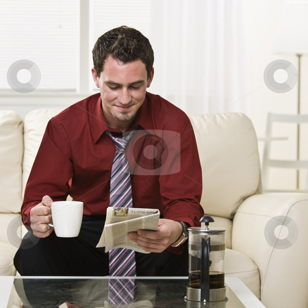 Attractive male drinking coffee and reading a newspaper stock photo, Attractive brunette male drinking coffee and reading the paper while sitting on the coach. square by Jonathan Ross