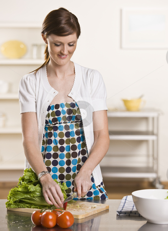 Brunette cutting radish. stock photo, Brunette making a salad in the kitchen slicing a radish, wearing a polka dot dress and white cardigan. vertical by Jonathan Ross