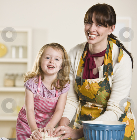 Mom and daughter making bread stock photo, Brunette mom and blond daughter making bread on the kitchen counter, while wearing aprons. Both are kneading dough and looking at the camera. Square by Jonathan Ross