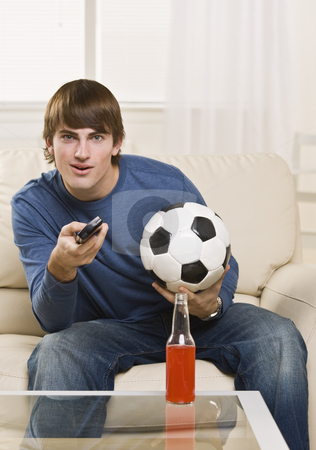 Attractive male with remote stock photo, Cute teenager with remote and soccer ball facing the camera, with drink on the table. vertical. by Jonathan Ross