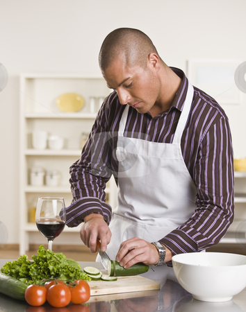 Attractive male cutting salad stock photo, Attractive male cutting salad on the kitchen counter while drinking a glass of wine. vertical. by Jonathan Ross