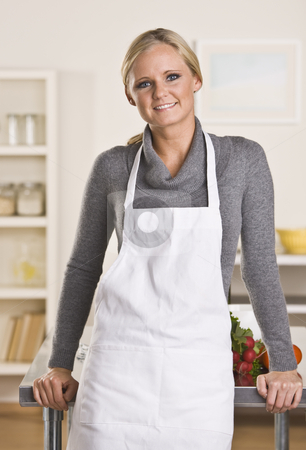 Attractive blond chef stock photo, Young attractive blond with apron in the kitchen, leaning on the counter. by Jonathan Ross