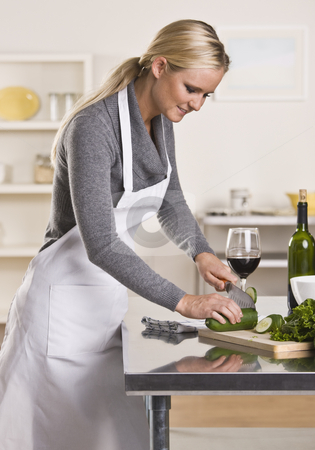 Attractive blond slicing cucumber. stock photo, Attractive blond woman slicing cucumber in kitchen while drinking glass of wine looking down.  Vertical by Jonathan Ross