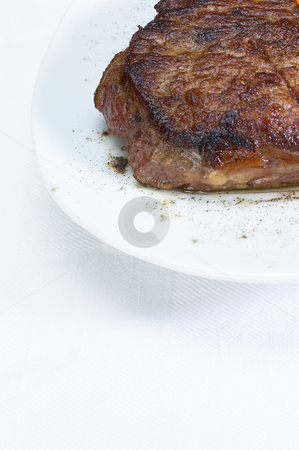 Beef ribeye steak stock photo, Fresh juicy beef ribeye steak grilled on a plate over a table by Francesco Perre