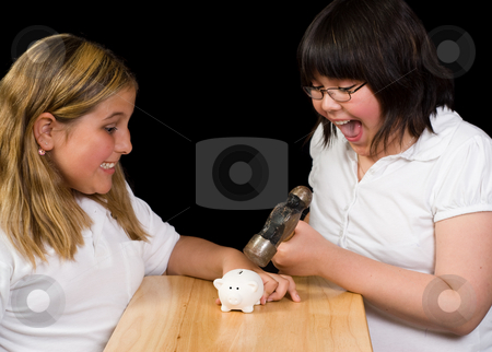 Payday stock photo, Two children using a hammer to break open a small piggy bank, shot against a black background by Richard Nelson
