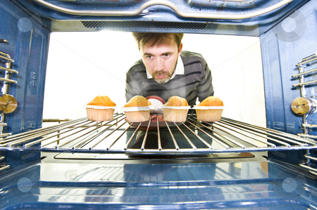 Unique viewpoint from inside an oven stock photo, A unique viewpoint from inside an oven while a man removes some freshly baked cupcakes. by Nicolaas Traut