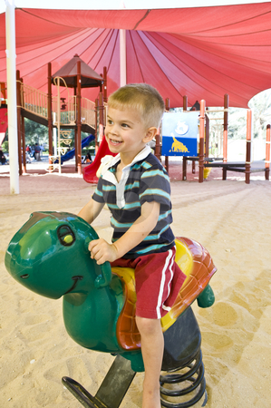Boy playing on a rocking horse stock photo, Little boy playing on a rocking horse in a park. by Nicolaas Traut