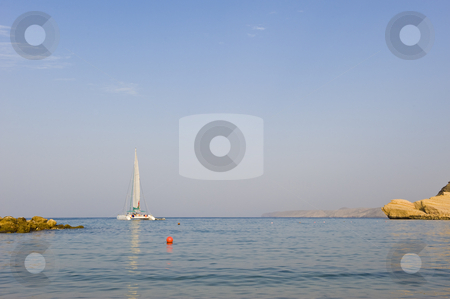 Sailboat anchored in a secluded bay area. stock photo, A sailboat anchored in a secluded bay next to the beach. by Nicolaas Traut