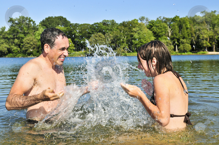 Family splashing in lake stock photo, Father and daughter splashing in a lake by Elena Elisseeva