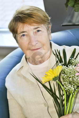 Elderly woman with flowers stock photo, Elderly woman holding bouquet of flowers and smiling by Elena Elisseeva