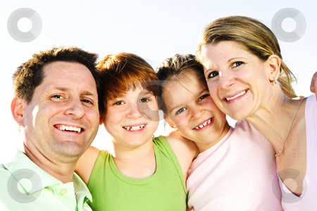Happy family stock photo, Portrait of happy family of four hugging and smiling by Elena Elisseeva