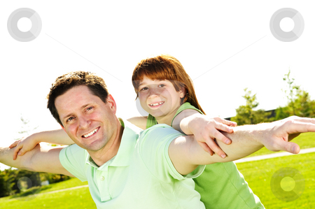 Father and daughter piggyback stock photo, Portrait of happy father giving piggyback ride to child by Elena Elisseeva