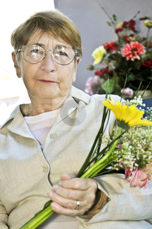 Elderly woman with flowers stock photo, Elderly woman with glasses holding flowers and smiling by Elena Elisseeva